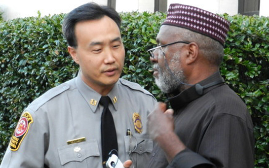 Imam Johari speaks with a police officer on the scene.